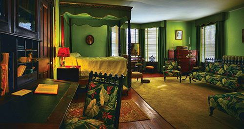 The photo of ancient bedroom furnishings that include bold green and red floral patterns.