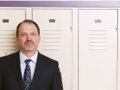 Photo of Harvey Bischof standing in front of lockers at Dunbarton High School