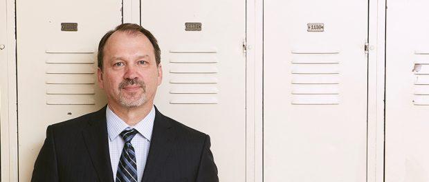 Photo of Harvey Bischof standing in front of lockers at Dunbarton High School