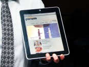 Image of a man holding an iPad displaying the education-forum.ca homepage.