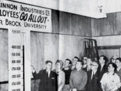 Vintage photo of McKinnon Industries employees admiring their fundraising thermometer chart.