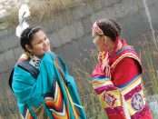 Photo of two teen First Nations girls dressed in traditional indigenous outfits.