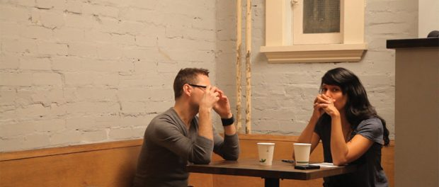 Photo of Attiya and Steve sitting at across from each other at a coffee shop.