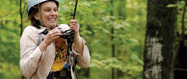 Image of teen zip lining in the forest