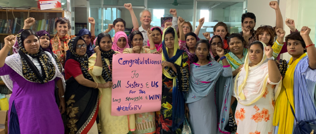 A photo of union leaders and the joint delegation standing in solidarity at the BCWS offices in Dhaka